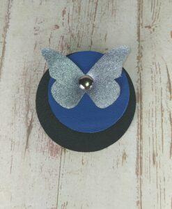 broche ronde en cuir bleu Klein et noir avec un papillon en cuir bleu métallisé